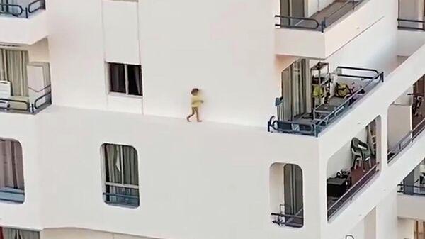 Стоп-кадр видео, на котором ребенок бежит по выступу здания на четвертом этаже