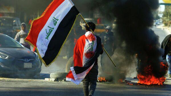 Мужчина с иракским флагом во время продолжающихся демонстраций на улицах Ирака. 12 января 2019