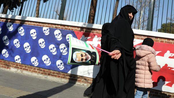 Женщина возвращается с похорон генерала Касема Сулеймани мимо посольства США в Тегеране
