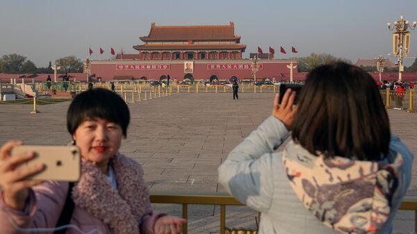 Девушки фотографируются на площади Тяньаньмэнь в Пекине