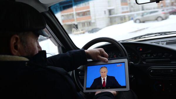 Житель Екатеринбурга смотрит трансляцию ежегодного послания президента РФ Владимира Путина к Федеральному собранию