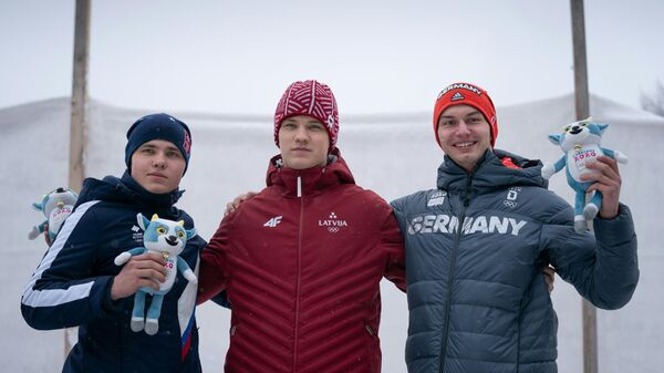 (from L) second-placed Russia's Pavel Repilov, first-placed Austria's Florian Tanzer and third-placed Germany's Timon Grancagnolo posing with the mascot during the podium ceremony after competing in the Luge Men's Single event on the St Moritz Olympia Bob Run, in Saint Moritz, during the 2020 Lausanne Winter Youth Olympic Games on January 18, 2020. (Photo by Thomas LOVELOCK / OIS/IOC / AFP) / RESTRICTED TO EDITORIAL USE - MANDATORY CREDIT AFP PHOTO / OIS/IOC / Thomas LOVELOCK - NO MARKETING - NO ADVERTISING CAMPAIGNS - DISTRIBUTED AS A SERVICE TO CLIENTS