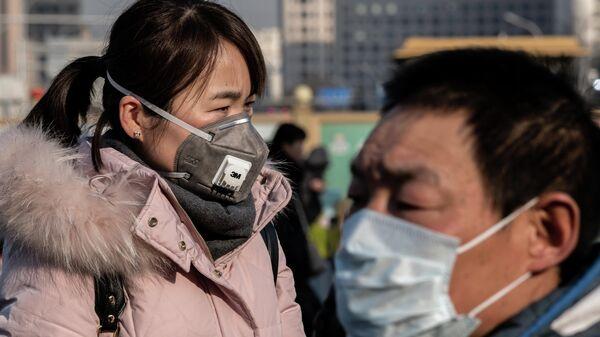 Женщина в защитной маске на железнодорожном вокзале Пекина, откуда множество людей отправляется домой на новогодние праздники. 21 января 2020