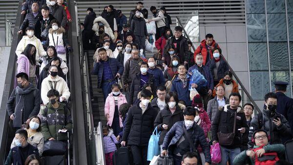 Пассажиры в масках на железнодорожном вокзале в Шанхае