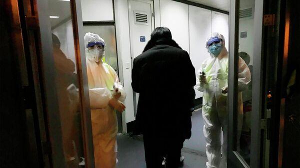 Медицинские работники в спецкостюмах проверяют температуру тела пассажиров, прибывающих из города Ухань в аэропорту Пекина