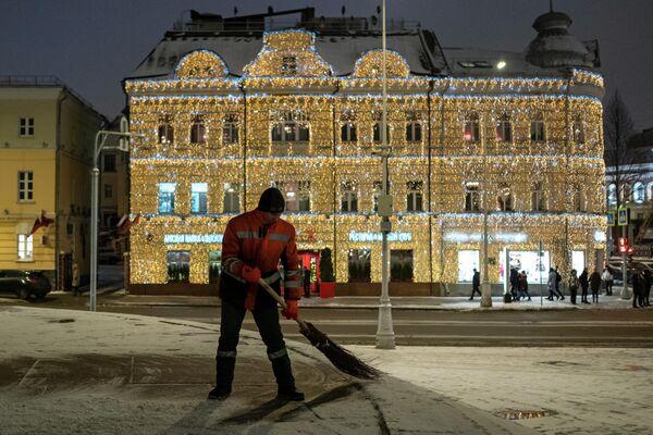 Сотрудник коммунальной службы подметает тротуар на улице Пречистенка в Москве