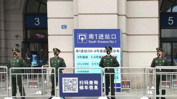 Военные полицейские у входа на закрытый железнодорожный вокзал города Ухань в провинции Хубэй