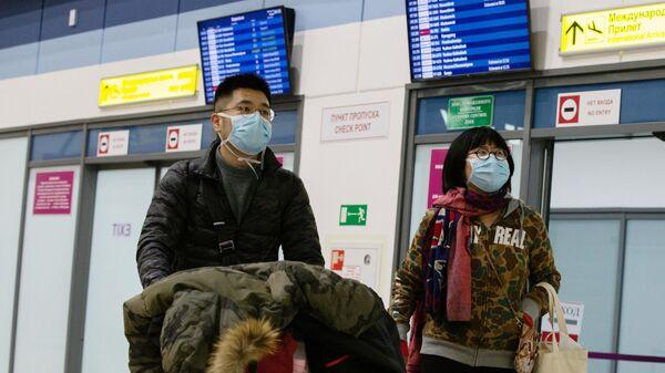Пассажиры в защитных масках в международном аэропорту Владивостока