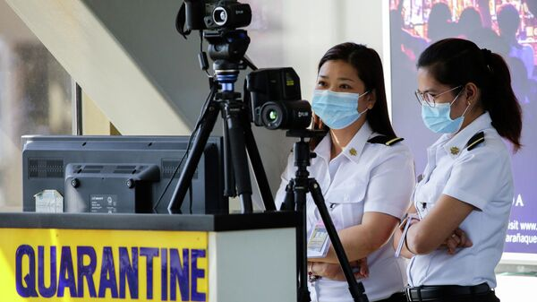 Сотрудники аэропорта следят за тепловым сканером в международном аэропорту Манила имени Ниноя Акино