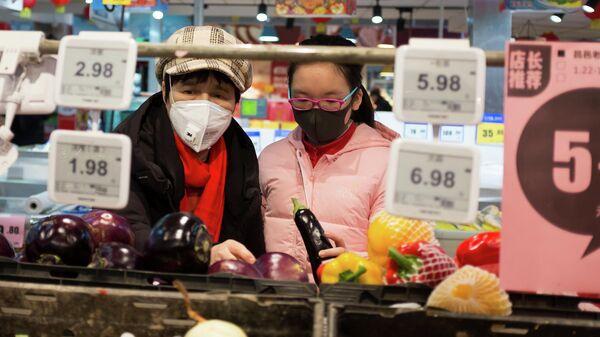Покупатели выбирают продукты в супермаркете в Пекине, Китай. 25 января 2020