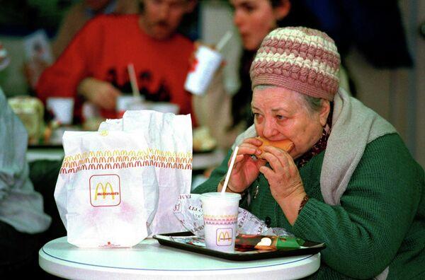 Женщина ест гамбургер в первом Mcdonald's в Москве. 31 января 1990 года