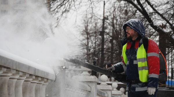 Сотрудник коммунальной службы чистит парапет у Александровского сада в Москве от снега