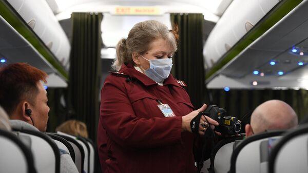 Сотрудница Роспотребназдора обследует при помощи тепловизора пассажиров