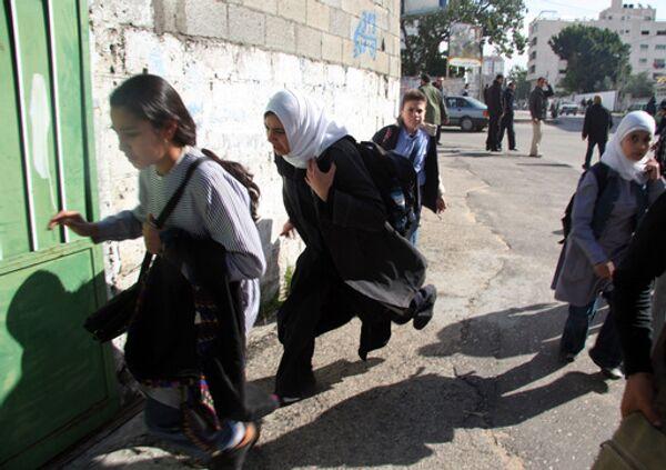 Палестинские женщины и дети бегут в укрытие во время авиаударов израильских ВВС