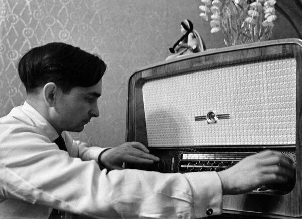 Лётчик-космонавт Валерий Быковский слушает радиоприёмник. Архив