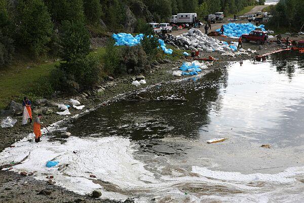 Сотрудники МЧС РФ с помощью абсорбента ликвидируют масляное пятно на реке Енисей