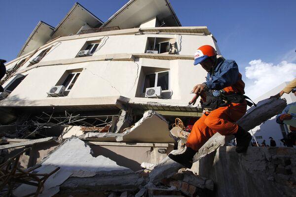 Спасатели из Японии во время осмотра завалов в индонезийском городе Паданг на Суматре