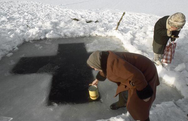 Верующая женщина набирает воду из озера. Архив РИА Нвоости