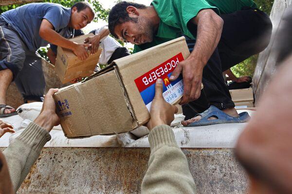 Жители города Ош разгружают грузовик с гуманитарной помощью из России. архив