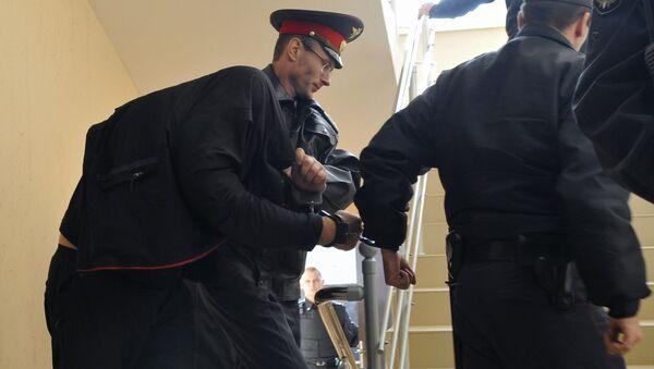 Сотрудники милиции ведут одного из главных подозреваемых в деле об убийстве 12 человек в станице Кущевская, архивное фото