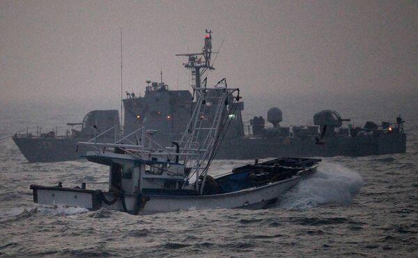 Рыбацкая лодка и патруль южнокорейской морской пехоты в водах Желтого моря