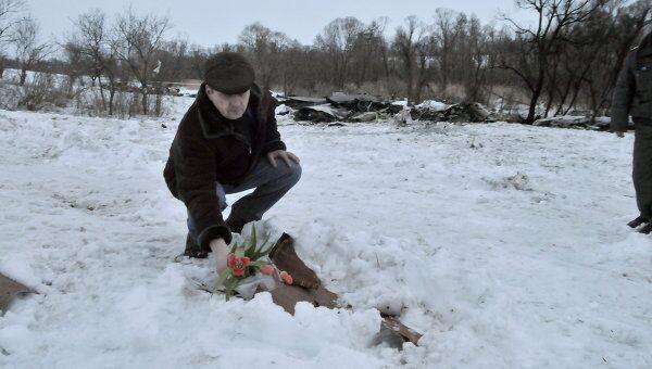 Местный житель кладет цветы на месте крушения Ан-148