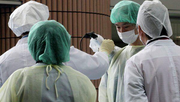 Специалисты проверяют эвакуированных людей на предмет заражения радиацией
