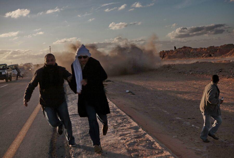 Мужчины бегут от взрыва ракеты во время боев за город Бин Джавад