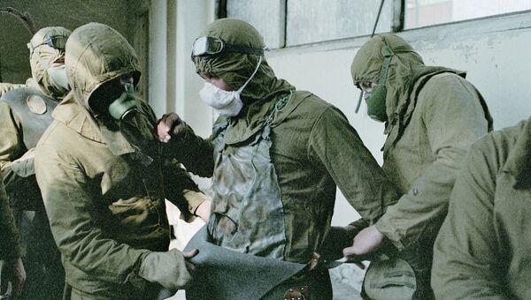 Люди, занимающиеся расчисткой кровли повреждённого реактора, одевают защитные костюмы. Архив