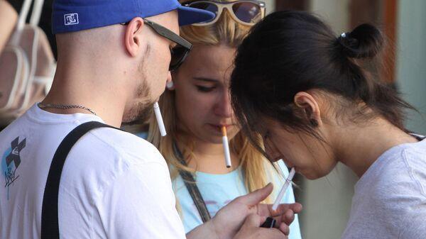 Молодые люди курят у входа в торговый комплекс
