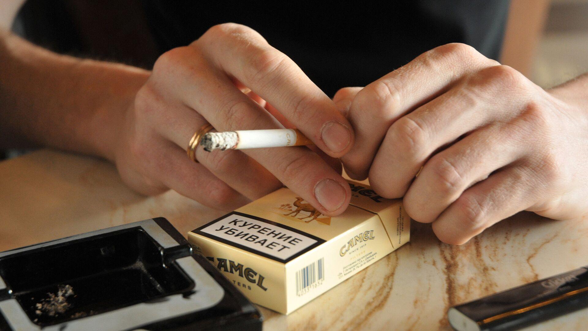 Мужчина держит в руках сигарету - РИА Новости, 1920, 24.12.2020