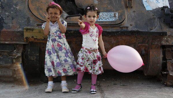 Ливийские дети играют на фоне сгоревших танков Муамара Каддафи