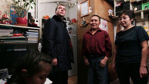 Президент России Дмитрий Медведев (слева) во время осмотра ветхой квартиры, где живет семья Николаевых