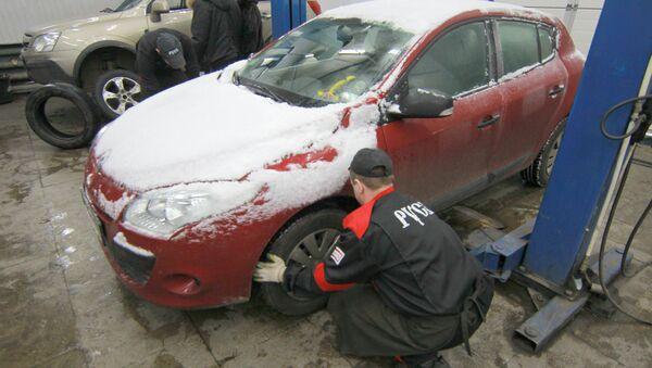 Работники шиномонтажа ведут работы по замене летней резины на зимнюю.