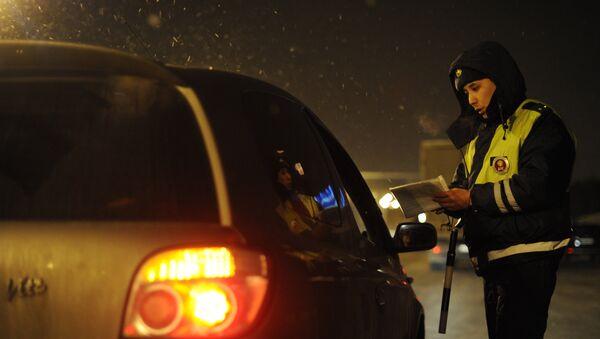 Сотрудник ДПС проверяет документы у водителя. Архивное фото