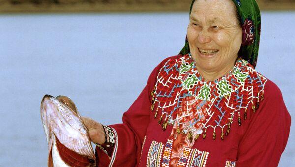 Женщина в национальной одежде держит щуку. Архив