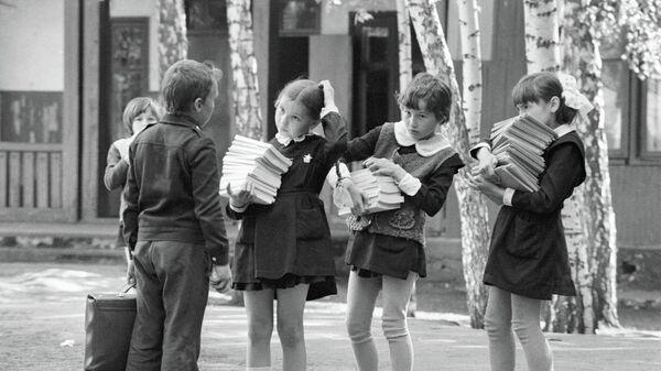 Школьники несут стопки учебников