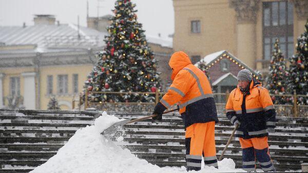 Сотрудники коммунальной службы чистят тротуары от снега в Москве