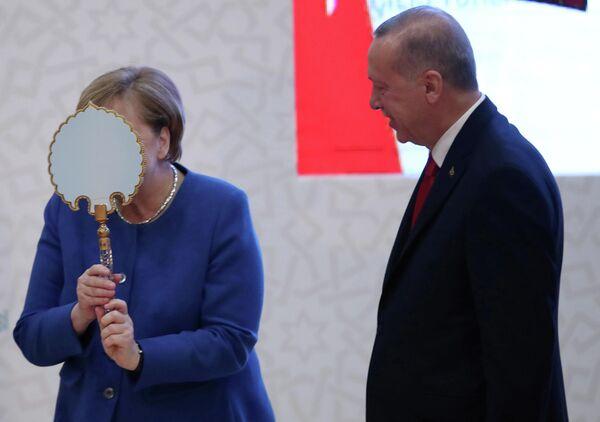 Канцлер Германии Ангела Меркель получает подарок от президента Турции