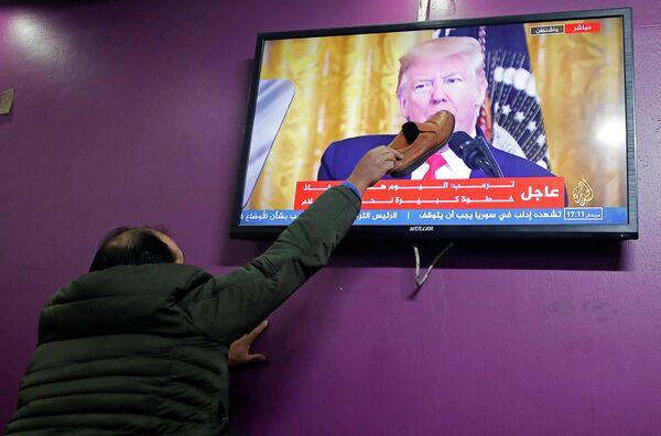 Палестинец смотрит выступление президента США Дональда Трампа по урегулированию палестино-израильского конфликта в кафе Хеврона