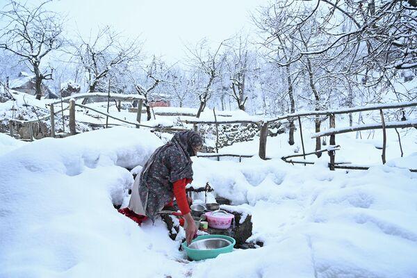 Женщина моет посуду после снегопада на окраине Сринагара в Индии
