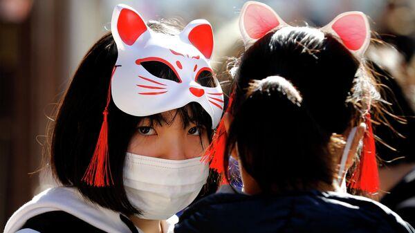 Девушки в защитных масках в Токио