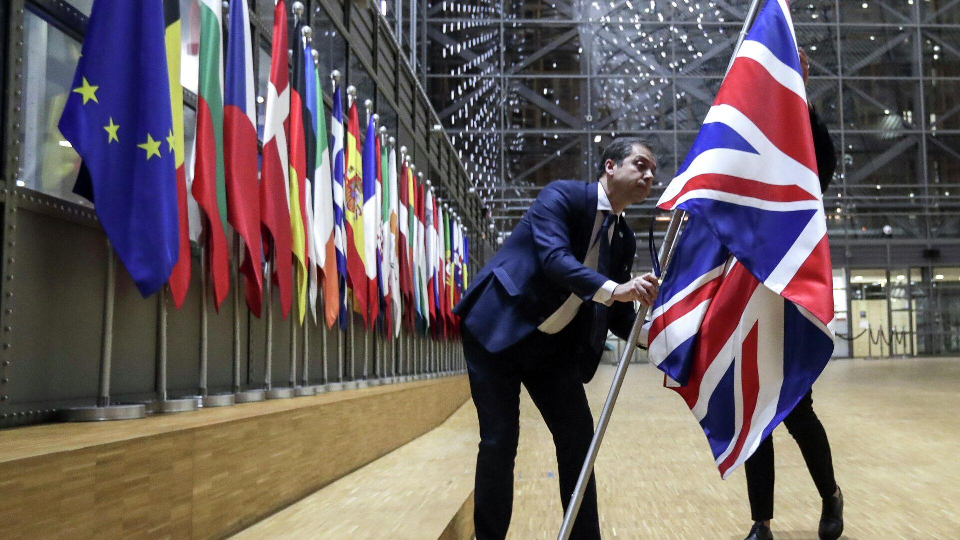 Сотрудники протокола убирают флаг Великобритании у здания Европы в Брюсселе - РИА Новости, 1920, 24.12.2020