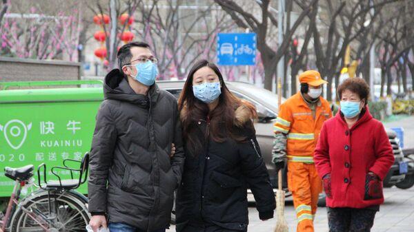 Прохожие в медицинских масках на улице Пекина, КНР
