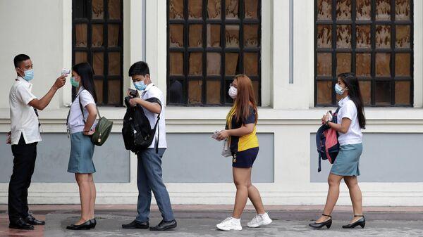 Медицинский работник проводит осмотр на входе в школу в Маниле, Филиппины