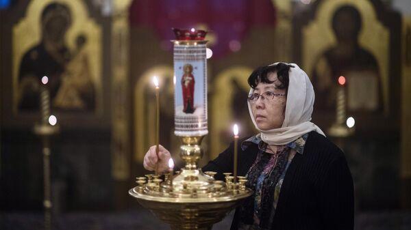 Женщина во время молебна о спасении от коронавируса в храме Святителя Николая в Голутвине на китайском подворье в Москве