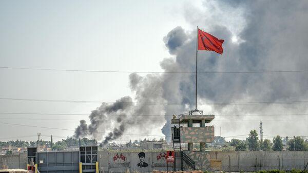 Дым на месте обстрела в районе границы Турции и Сирии