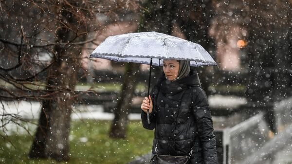 Женщина идет с зонтом во время снегопада в Москве