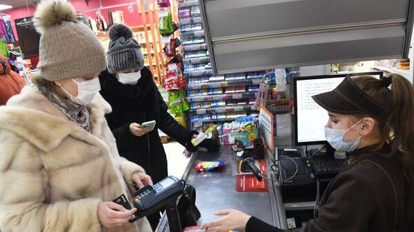 Покупатели в медицинских масках на кассе супермаркета Караван в Чите