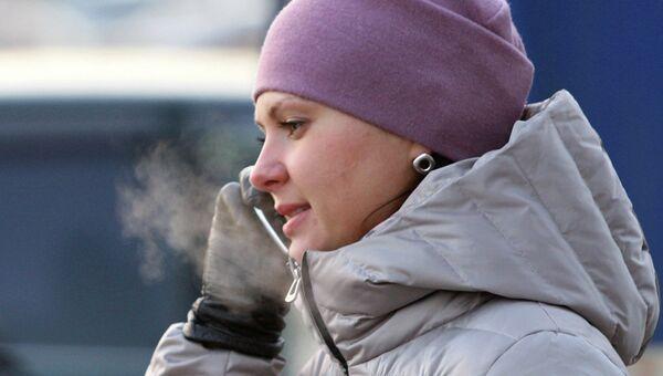 Девушка говорит по телефону в мороз на остановке автобуса в Новосибирске. Архив